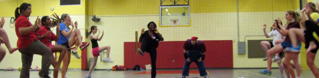 A self-defense instructor trainee teaches a class how to stomp on an attacker.