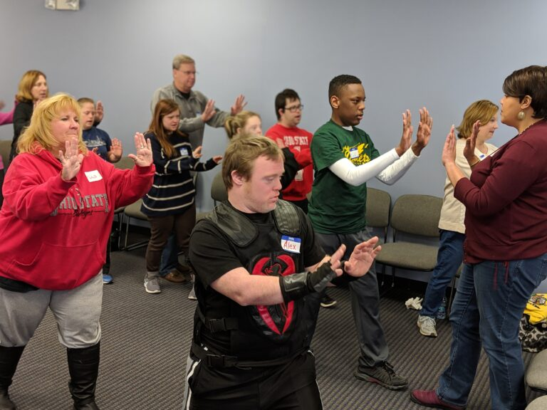 Teens with Down Syndrome learn from an IMPACT self-defense trainer.